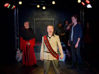 King John in tan uniform jacket and olive pants and a red and black sash across his chest stands front and center yelling; behin him to his right, the Cardinal is in red cardinal robes with black stole; to John's left King Philip in blue jeans, blue shirt and blue tee. The platform with bordered by chain link fences is at the back of the stage, sandbags at the base, and other cast members lined up against the backstage wall.
