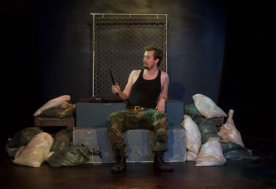 Philip the Bastard in black tanktop and camouflage soldier's pants holds a knife in his right hand as he looks upon it, sitting on the platform surrounded by sandbags and a chainlink fence behind him.