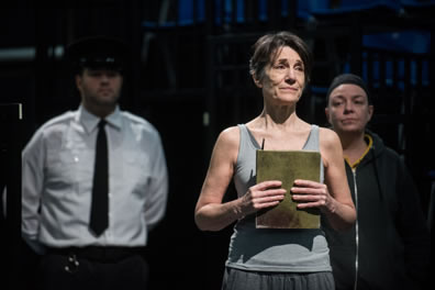 Hanna/Prospero in gray tanktop and sweatpants clutching a book, with a guard in white shirt, black tie and police hat behind her on the left, the inmate playing Calaban in black jacket and black stocking cap behind her on the right