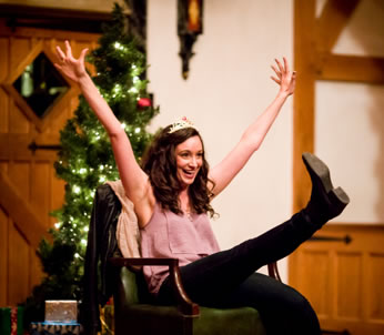Mary in chiffon pink tank top, black jeans and boots and wearing a tiara sits in a green chair, right leg kicking out and both arms raised in the air with a Christmas tree behind her.