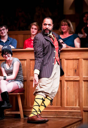 Leaning sideways against the theater wall, Malvolio in blue striped suit jacket, red patterend vest, red tie, tan knee pants, poins down to his yellow-stockinged, cross-gartered shins. Laughing girl sitting on gallant stool next to him, other audience in the background.