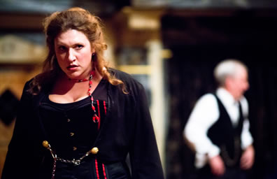 Kate in Victorian black dress with red streaks and red and blue braids scowls while in blurry background stands Petruchio in black vest and white shirt