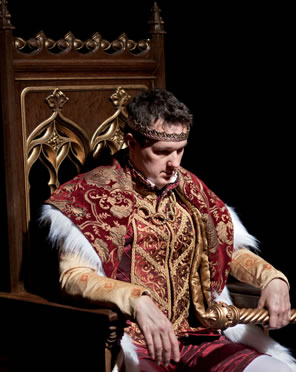 King John in ornate royal robes sitting on a throne with his head down pensivelyh