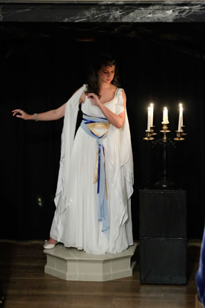 Hermione in Gree-like gown posing as the statue, on a pedestal with a candelabra next to her