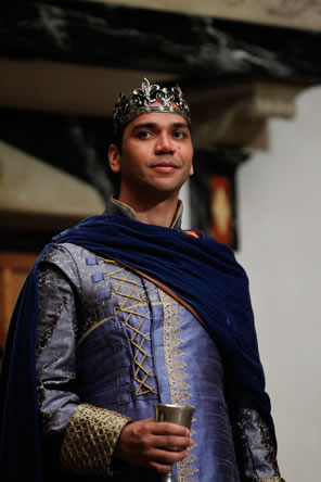Leontes in purple royal clothes holding a cup of wine