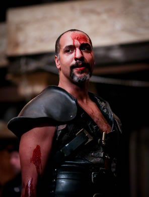 Coriolanus in black armor-like leather vest, blood on his arm, and blood dripping down his face from his forehead.