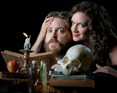 Mephistopheles with her check pressed against Faustus's temple, her right hand hugging his head, he's sitting at a desk with a book open, a candle, a skull on stacked books, an apple on another stack of books, and vials between the stacks