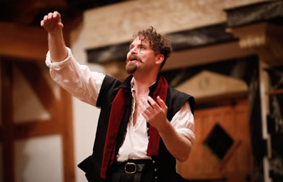 Hamlet looking up, motioning with both arms, wearing white shirt, black renaissance vest and  a red scarf draped over his shoulder