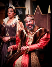 Lear sitting on throne, with gold crown, brown fur robe, gold chain, red shirt and gown, speaking in anger as Goneril in the background, wearing a purple Jacobean dress with gold sleeves, gold medalina, gold tiara, and upturned collar.