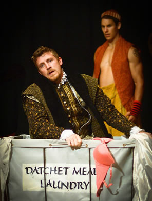 "Ford in richly embroidered tudor cloak looking forlorn as he kneels in the laundry basket, which has a pink bra hanging over the front. Stenciled on the basked is ""Datchet Mead Laundry."" In the background is the servant, shirtless with orange vest and baggy yellow pants"