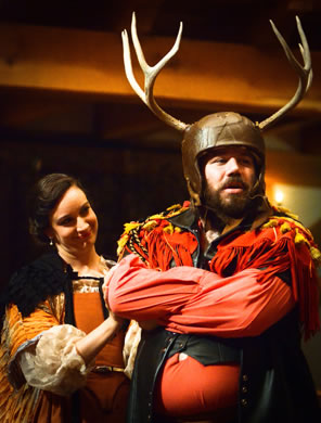 Falstaff wears helmet with a hide covering and 6-point antlers, has his arms crossed waring a tasled red shirt with leath vest, Mistress Ford in elaborat orange dress and white puff sleaves looks sweetly at him