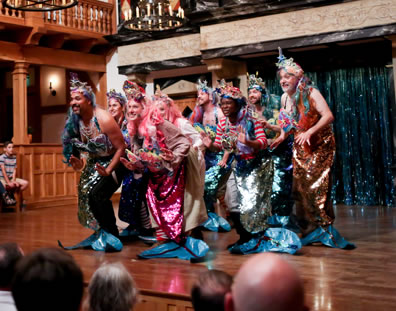 Nine mermaids, each in multi-colored metalic fins with blue flippers and various crowns, dance in a diamond on the center of the stage, with audience sitting on the stage behind and chandeliers of the Playhouse hanging overhead.