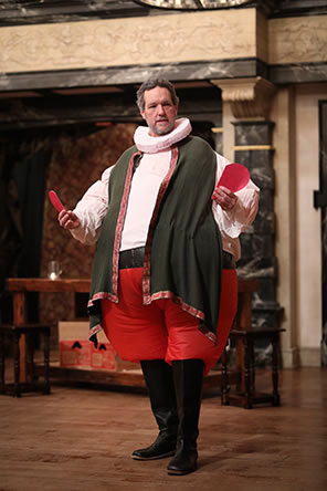 Production photo of Falstaff holding two halves of a red paper heart