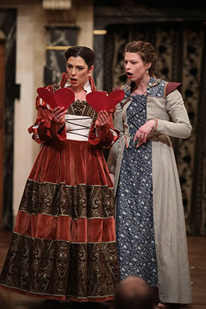Production photo of Alice Ford and Margaret Page looking at the notes from Falstaff, each opened to form a full heart.