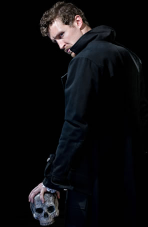 Hamlet in black coat, collar up, looking back over his shoulder at the camera, a skull gripped in his left hand dangling at his side