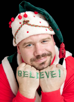 "Rick Blunt in elf costum, fists to chin with ""Believe"" tatooed in green on his knuckles"
