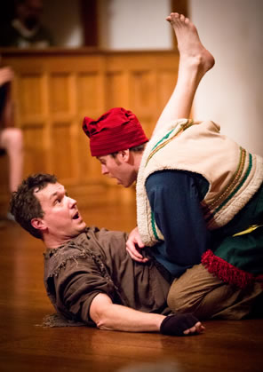 Autylocus in bran ragged clothes on his back as Clown sits astride him, pushing up the rogue's leg: Clown in red stocking cap and fur lined layered peasant clothes
