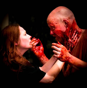 Lady Macbeth, hair down, blood on hter chin and nose, places her bloody hands around Macbeth's neck, as he, holding bloody hands up, looks into her face.