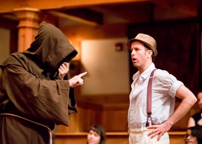 Duke hooded face totally covered in hood of his monk's habit, gestures with a pointed finger as Lucio, hands on hips, wearing whit work shirt and white pants, with suspenders and fedora, looks in astonishment.