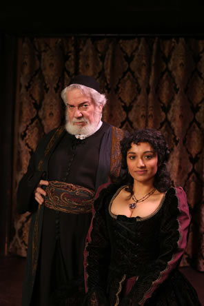 White bearded Shylock in black robe and skullcap with paisley patterned robe and belt poses with Portia wearing a black dress with gold trim and purple sleeves.