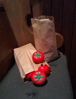Two bags of foam tomatoes on a cushioned church pew