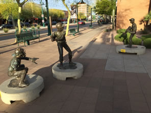 Photo of three statues of children playing baseball