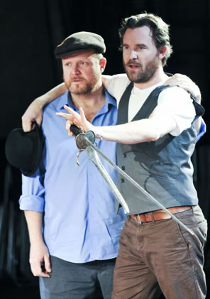 Hamlet in vest and brown jeans holding a sword and dagger with his arms around Horatio in Irish cap and blue shirt, a bowler gripped in Hamlet's other hand.