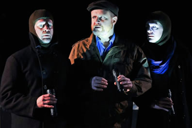 Actors in overcoats and stocking hoods hold flashlights casting lights onto their faces