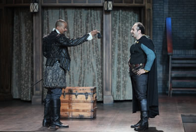 Burbage in Elizabethan leather jacket, bulging knee britches and boots holds out a black purse to Shakespeare in jacket vest over blue shirt and black pants with boots and long cloak. A wood trunk is on the stage.