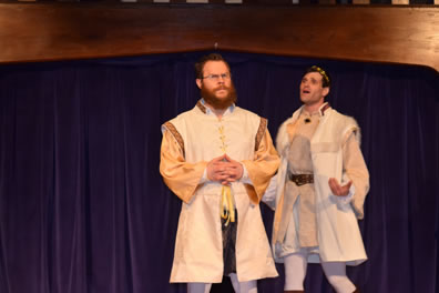 Leontes to the right with hands cupped and outstretched in exasperation talking to the side of Camillo, who patiently holds his hands folded at his waist, both where white sleeveless tunics with satiny shirts underneath and white leggings, Leontes in a crown.