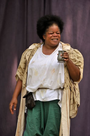 Falstaff, with white puffy shirt, green pants, black coin purse hanging on her string belt, and a tapestry like cloak holds up a pewter mug