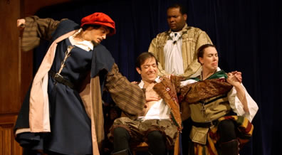 Shylock in blue renaissance robe with brown striped sleeves and red cap holds back the knife with hir right hand and has his left palm on Antonio's bare breast; Antonio sitting, wincing at what's coming, holding the hands of Salarino, while the Duke of Venice in gold robes holds Antonio's shoulder