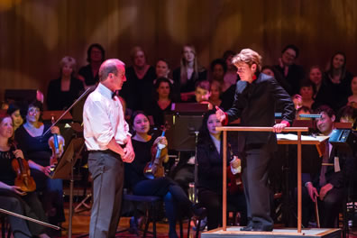 Alsop in a black pants suit stands on the podium, one hand on the railing, as white-shirted Bolger stands meekly, hands at waist, as violinists and choral members watch in the background