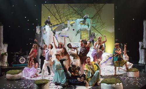 The whole cast in various poses and various costumes, confetti coming down, the stone set in the background in front of a yellow sky and web-like sticks sculpture, the four white boulder around the floor, and two white tree trunks to each side of the stage.