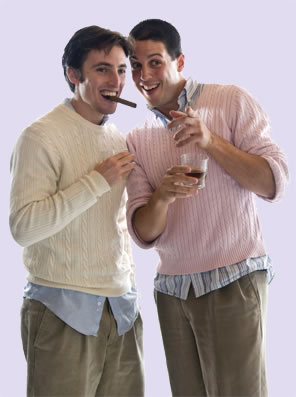 Proteus, with cigar in his mouth, talks closely with Valentine, drink in hand, both in sweaters over oxford shirts with shirttails hanging out and pleated trousers