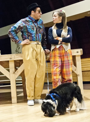 Launce and Speed stand against a platform, he in multi-blue-colored shirt and baggy gold pants, she in orange checkered pants, blue shirt and vest, with Crap grazing in front of them