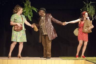 Falstaff in brown leather jacket and brown pants and shirt and hat holding a bagged liquor bottle holds the hands of Mistress Ford in green-patterned  knee-length dress and brown purse, and Mistress page in white polka dot red thigh-length dress, holding a bag of groceries, with hanging planters of ferns behind.