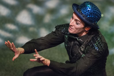Puck wearing his blue sequined bowler and green sequined vest squats with his hands expressively held out before him, and you can see the dappled light on the stage.