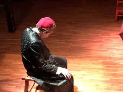 Shylock in black cloak and red skullcap sits on a bench