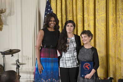 Michelle Obama in black tank top and red, blue dress with checked pattern and flowers, Jennifer MacCaskey in white with black cross patterend fblouse and black sweater and pants and cross necklace, Halperin in grey dress with black sleeves holding award. American flag behind first lady, gold curtain across the back to the right, drum set to the left.
