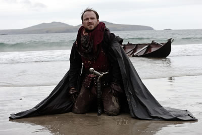 Bolingbroke in waistcost armor, sword in hilt, cloak about him, neals on a muddy beach with a boat in the surf behind him