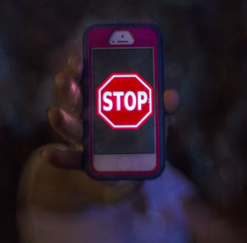 A hand holding to the camera a smartphone with a stop sign on the screen--looks graphic cartoon like