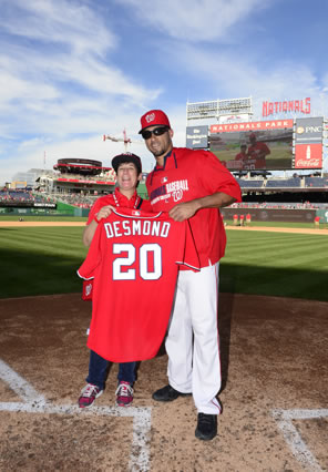 "Desmond in red W basball cap, sunglasses, windbreaker and white uniform hat next to big-smiling Sarah in baseball cap, red shirt, blue jeans, and spider sneakers, both holding the red baseball jersey with ""DESMOND 20"" on the back. This is at home plate with the baseball field, scoreboard, and Red Porch cafe and beautiful blue skies with whispy clouds in the background."