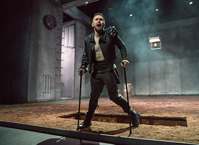 Production photo of Richard using his crutches as he stands in front of an open grave; his black Elizabethan jacket is unbuttoned showing his bare abdomen, and his left leg is crooked.