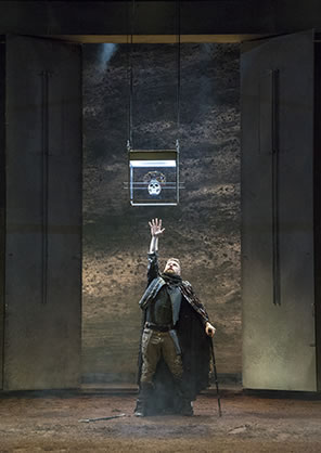 Production photo of Richard standing under the crowned skull in the glass box suspended from the ceiling. Richard is reaching up as high s he can with his right arm while his left arm leans on a crutch (the other crutch is at his feet on the dirt floor.