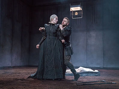 Production photo of Richard in black jacket and pants behind Lady Anne in simple black Elizabehtn dress. His hands are around his shoulder and his leg is crooked, the two crutches on the dirt bloor at his feet. Her head is turned looking at him. In the background is the white shrouded corpse of Henry VI.