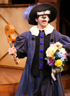 Il Dottore wearing a purple rennaissance robe with white frilly coller and huge blue buttons, a large-brim hat with purple feather, a mask featuring a black nose and huge white fluffy eyebrows and mustache. He's holding a ukelele by the neck in one hand and a bouquet of flowers in the other.