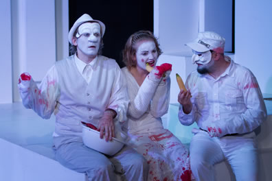 Marcus in fodor hat and vest and white face on the left holds a bowl; Lavinia in the center in white faced gnaws on an unpeeled banana; Titus  in commedia mask and soldiers hat holds a banana. He and Marcus are missing a hand, Lavinia missing both hands, and blood stains are on their white clothes.