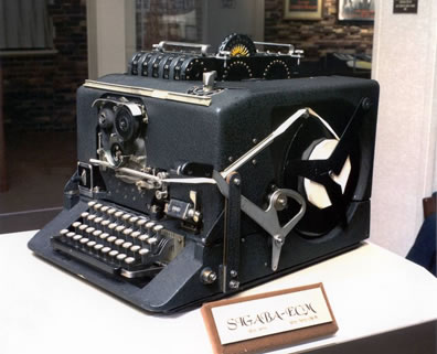 What looks like a big, boxy typewriter, with a computer tape spindel on the visibal side, and contraptions sticking out of the top, including disks