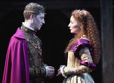 Henry in royal shirt and purple cape faces Katherin in bejeweled dress